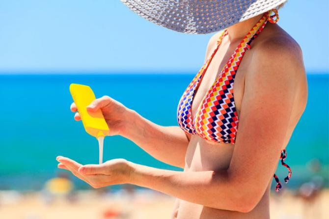 preventing aging hands with sunscreen on a beach